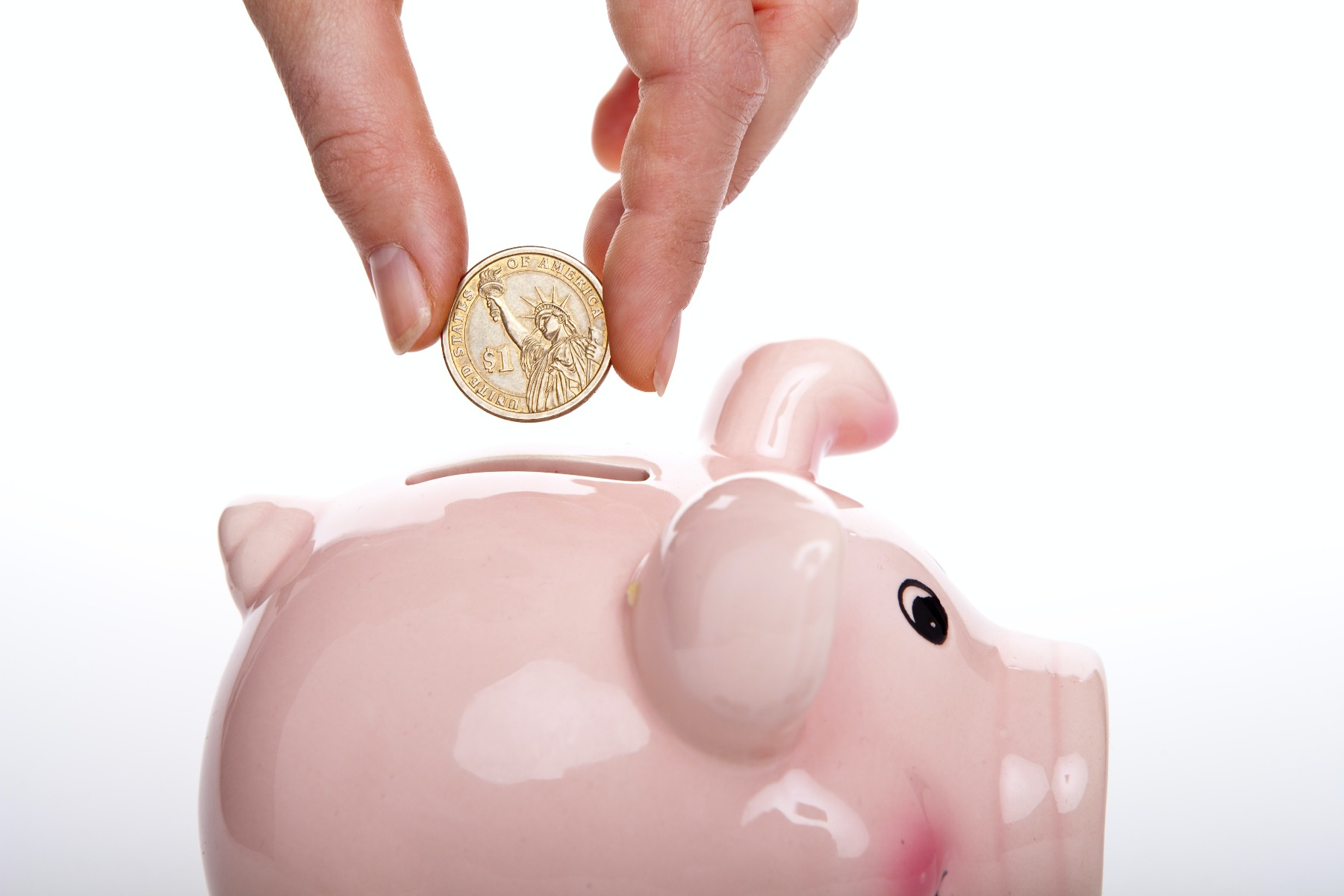 hand dropping $1 coin into pink piggy bank