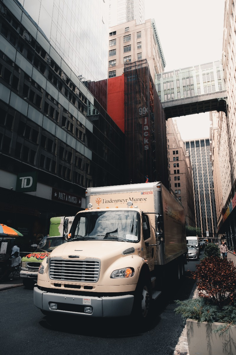 white freight truck driving through narrow city street with tall buildings on either side
