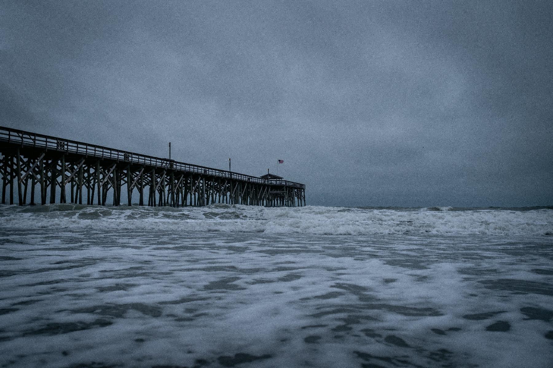 dark stormy sky and sea surrounding long pier extending into ocean