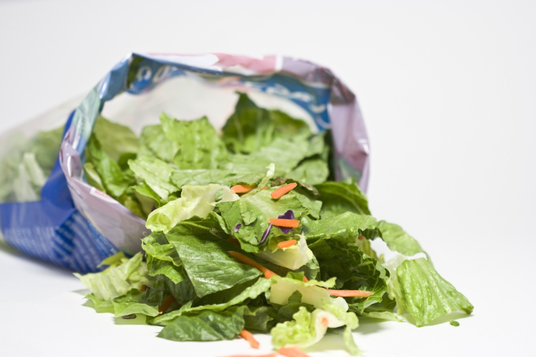 open bag of pre-made salad spilling onto white background