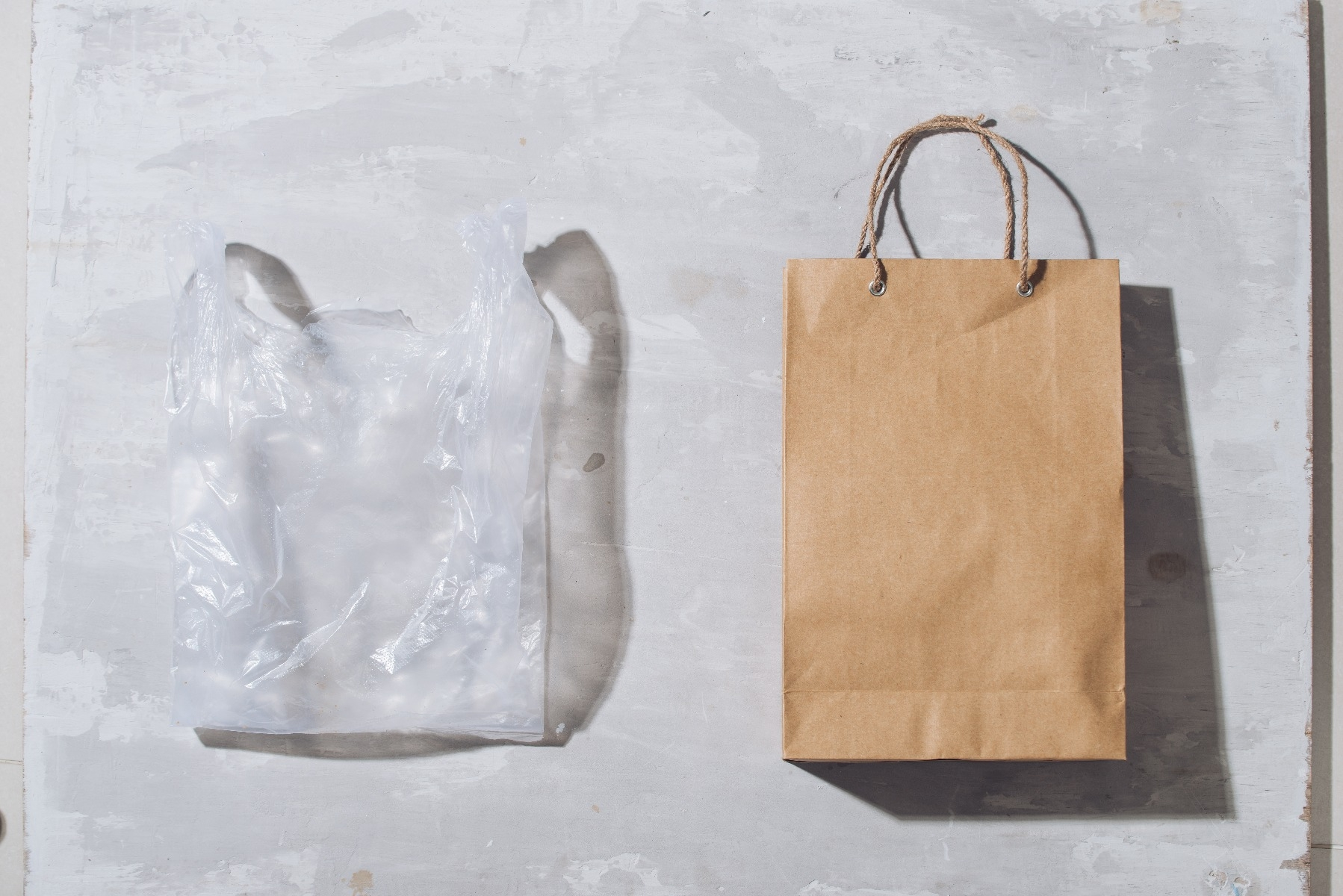 clear plastic bag and brown paper bag side by side on grey background