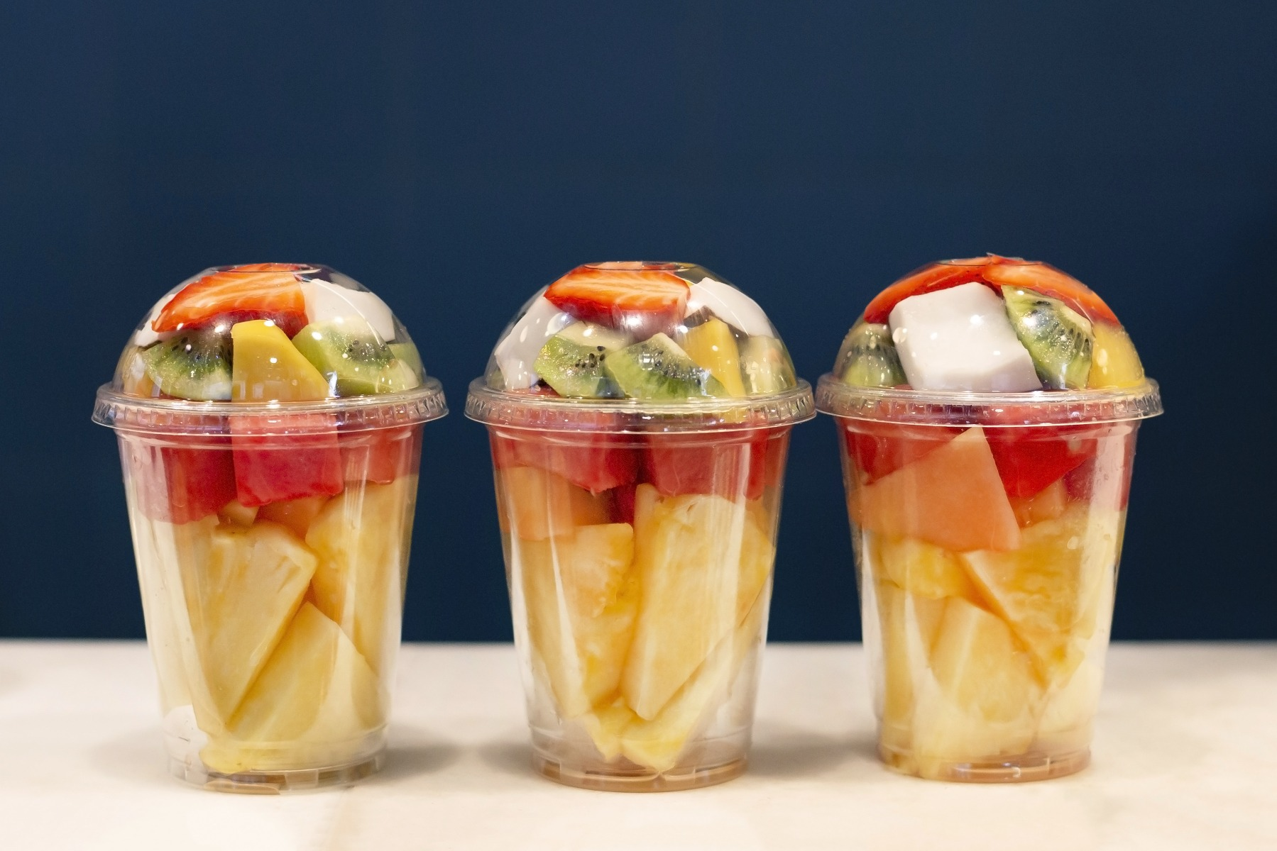 three sets of assorted pre-cut fruits in rigid plastic containers on table