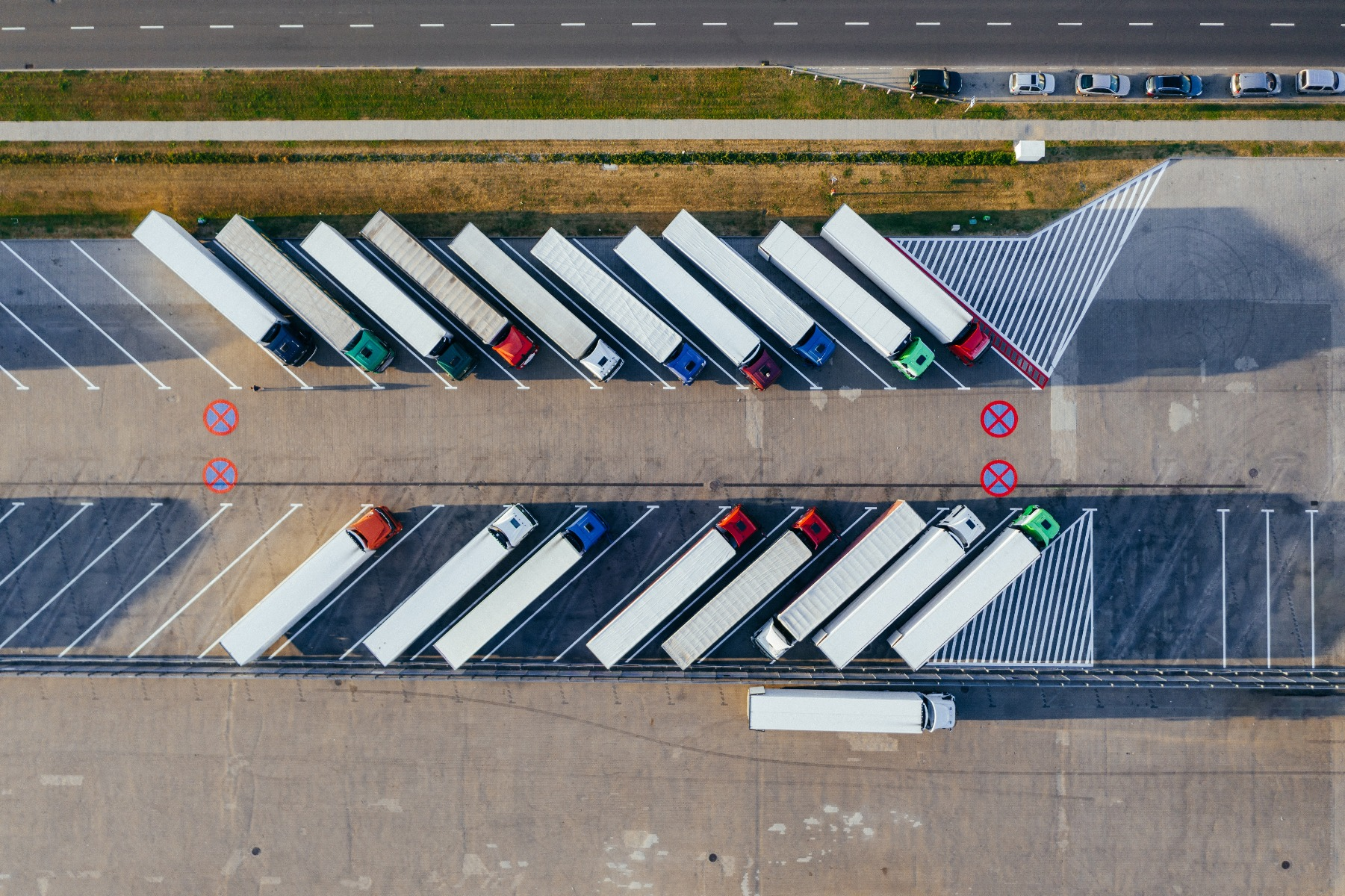 overhead image of semi truck trailers parked at angles back to back in parking lot