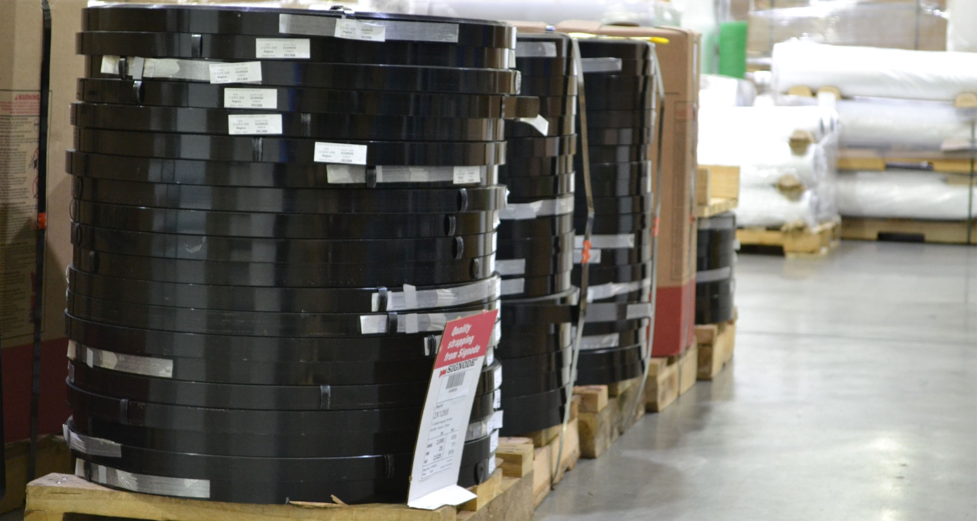 three coils of steel strapping sitting on pallets in warehouse