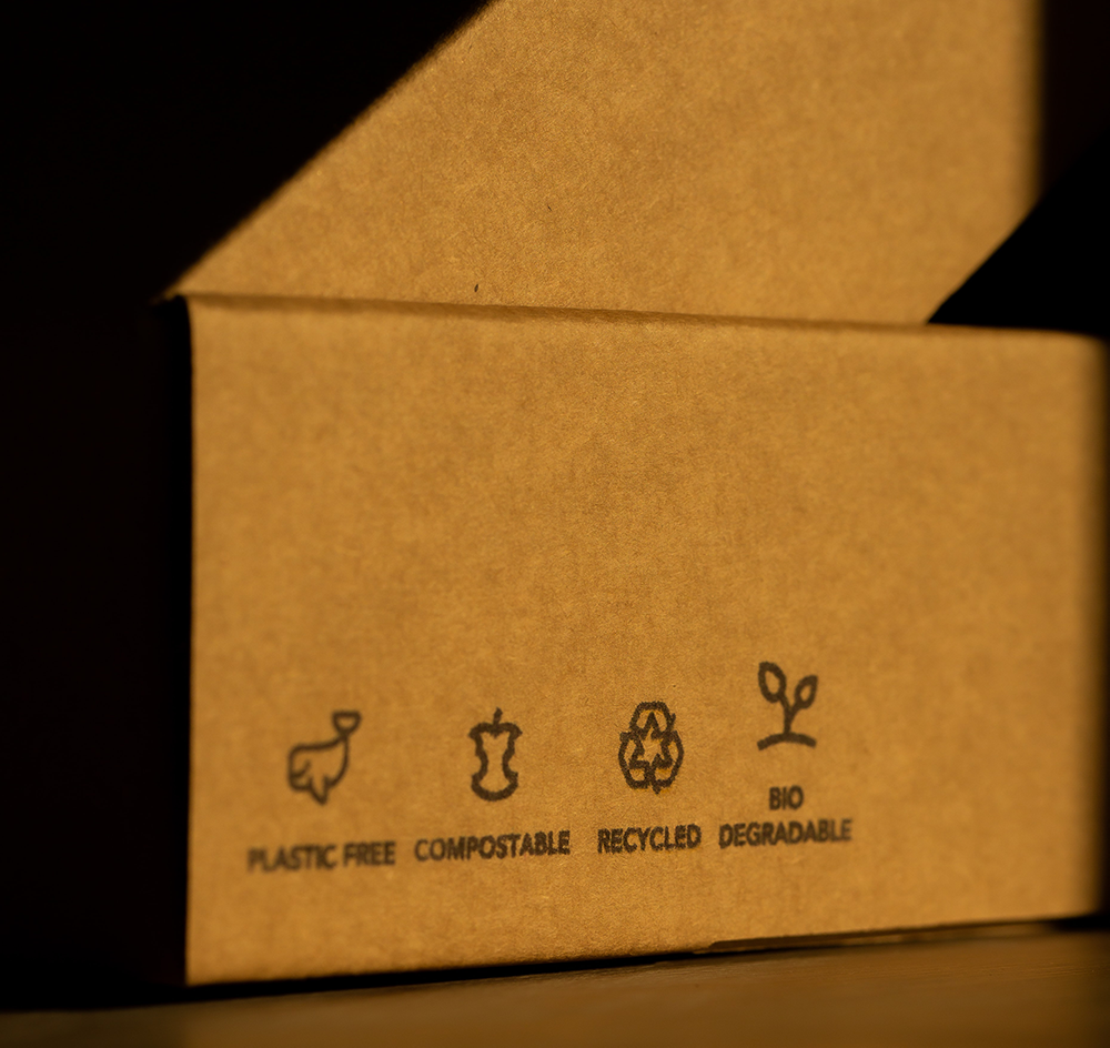 corrugated box on table with sustainable packaging stamps like plastic free and compostable