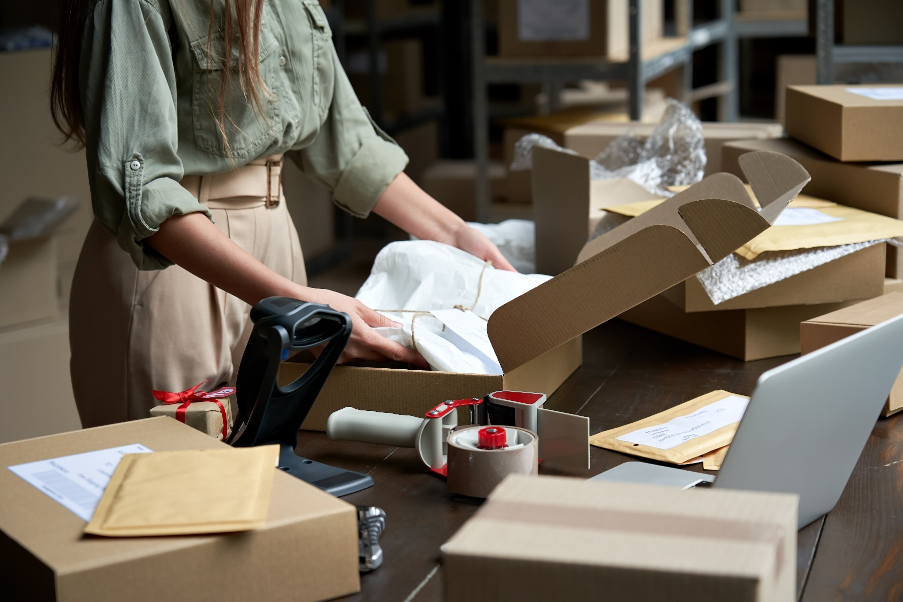 woman placing item wrapped in tissue paper into corrugated box with packaging supplies on table around it