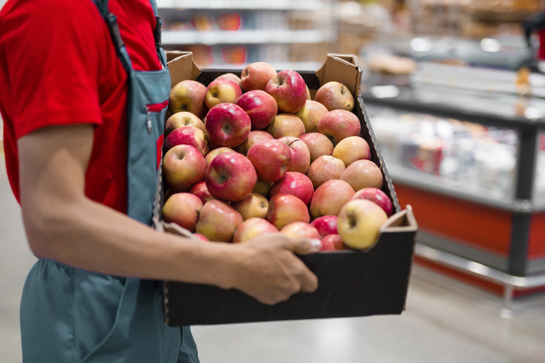 grocery employee carrying open retail ready corrugated box full of red apples