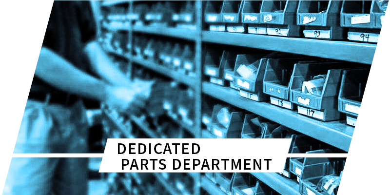 person searching through part containers on shelves with text dedicated parts department